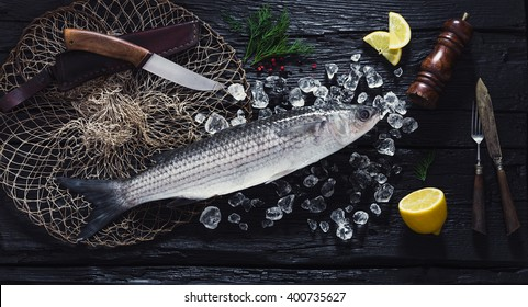Fresh liza fish on ice on a black wooden table top view