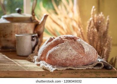 Fresh loaf of bread with grain and ears