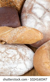 fresh loaves of different kinds of wheat and rye bread on a wooden surface, closeup
