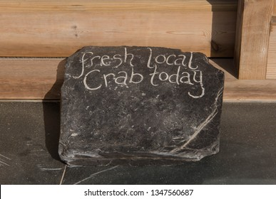"""Fresh Local Crab Today"" Hand Written on a Flint Stone at Chapel Porth Beach on the South West Coast Path between Perranporth and Portreath in Rural Cornwall, England, UK"