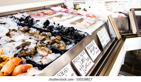 Fresh local seafood like salmon, pompano and oysters over ice on display with metal casing creating visual rhythm.