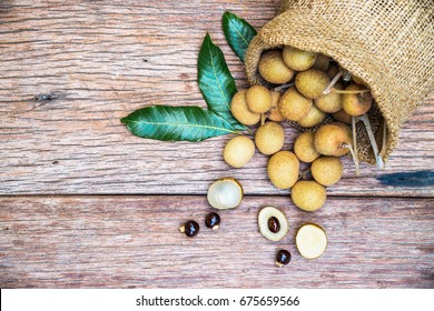 Fresh Longan (Dimocarpus longan) with sackcloth on a wooden background.