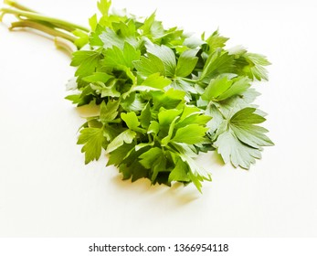 Fresh lovage celery stems with leaves on white wooden background. Shallow dof.