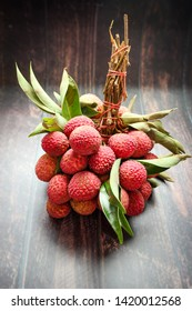 Fresh lychee fruits (Litchi) with leaves on wooden table