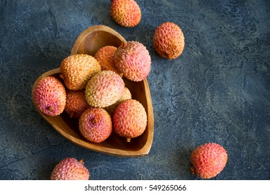 Fresh lychees in a bowl on a dark background. Top view with copy space