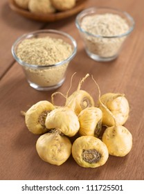 Fresh maca roots or Peruvian ginseng (lat. Lepidium meyenii) with maca products (maca powder, oatmeal with maca, maca cookies) in the back (Selective Focus, Focus on the maca roots in the front)