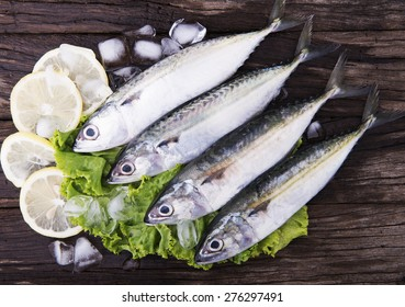 Fresh Mackeral on wooden background with lemon