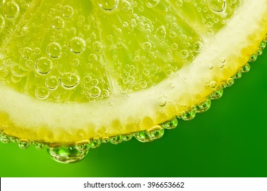 Fresh macro lemon with drops on a green background