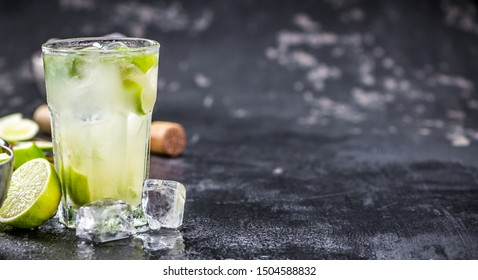 Fresh made Caipirinha with ingredients in the background.
