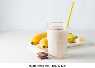 Fresh Made Chocolate Banana Smoothie on a wooden table. Selective focus. Milkshake with almonds. Protein diet. Healthy food concept.