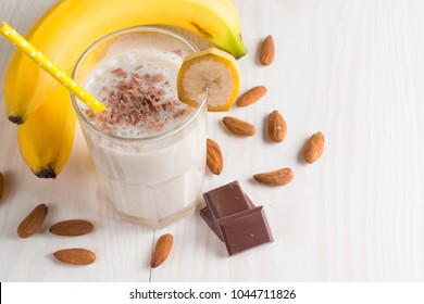 Fresh Made Chocolate Banana Smoothie on a wooden table. Selective focus. Milkshake with almonds. Protein diet. Healthy food and drink concept.