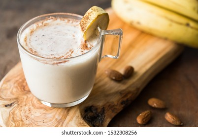 Fresh Made Chocolate Banana Smoothie on a wooden table. Selective focus. Milkshake with nuts. Protein diet. Healthy food and drink concept.