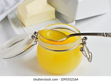 Fresh made clarified butter. Ghee butter in glass jar with vintage spoon.