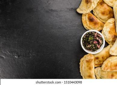 Fresh made Empanadas on a slate slab (close-up shot; selective focus)