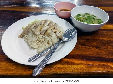 Fresh made Hainanese chicken rice serves with small bowl of hot soup and thai style salt and spicy soya bean sauce on wooden table.