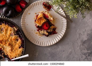 fresh made plum crumble on white plate on grey background. top view