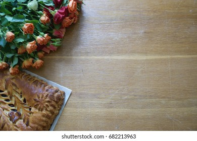 Fresh made yeast cake on the parchment and roses flowers, top view with copy space, full frame pic