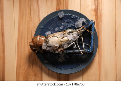 Fresh malaysian freshwater prawn with ice on wooden table, top view