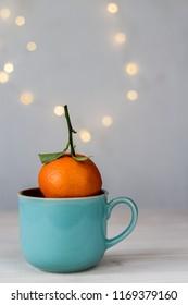 fresh mandarin in a ble ceramic mug on bokeh background