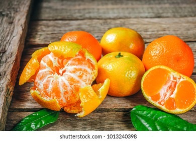 A lot of fresh Mandarin orange or mandarine with green leafs on wooden floor