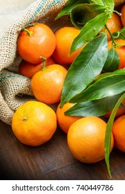fresh mandarin oranges fruit with leaves on wooden table