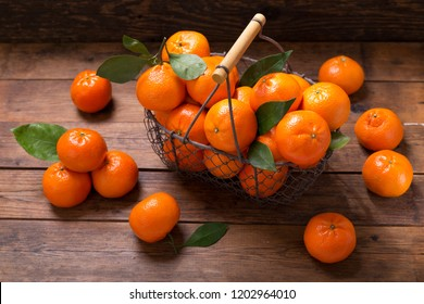 Fresh mandarin oranges fruit or tangerines with leaves in a basket on wooden table