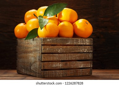 Fresh mandarin oranges fruit or tangerines with leaves in the wooden box