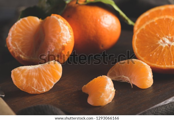 Fresh mandarin oranges or tangerines with leaves on textured dark background