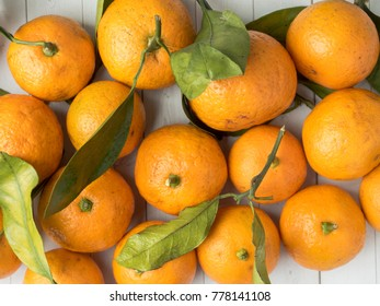 Fresh mandarin or tangerines with stems and leaves on white wooden background Copy space.