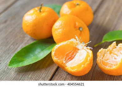 fresh mandarins with leafs on old wooden table