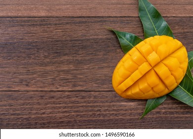 Fresh mango, beautiful chopped fruit with green leaves on dark wooden table background. Tropical fruit design concept. Flat lay. Top view. Copy space