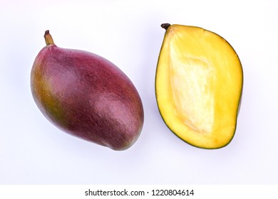Fresh mango cut in two parts. Two halves of ripe mango fruit on light background. Tasty and nutritious fruit.