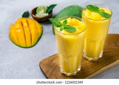 Fresh mango juice and mango fruit on grey background