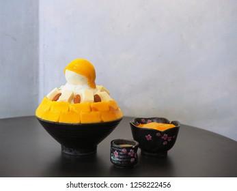 Fresh mango kakigori, The shaved ice layered with milk cream,  mango ice base, more sweet ripe mango cubes and topped with mango sauce. Trendy dessert in Thailand.