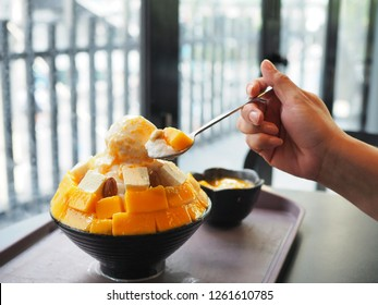 Fresh mango kakigori, The shaved ice layered with milk cream,  mango ice base, more sweet ripe mango cubes and topped with mango sauce. Trendy dessert in Thailand.
