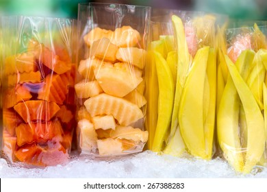 Fresh mango, melon and papaya fruits sliced in plastic bags in a street market.