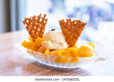 Fresh mango shaved ice with a scoop of ice cream and juice sauce in summer restaurant, lifestyle, popular food in Taiwan, close up.