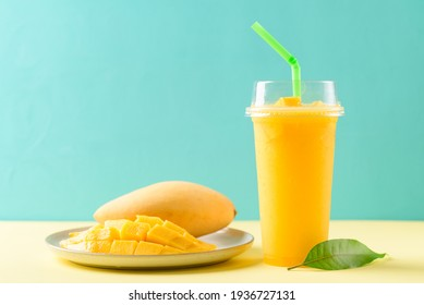 Fresh mango smoothie in a glass and sliced ripe mango fruit on color background, Tropical drink