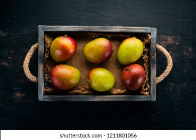 Fresh mango in a wooden box. On a wooden background. Tropical Fruits. Top view. Free copy space.