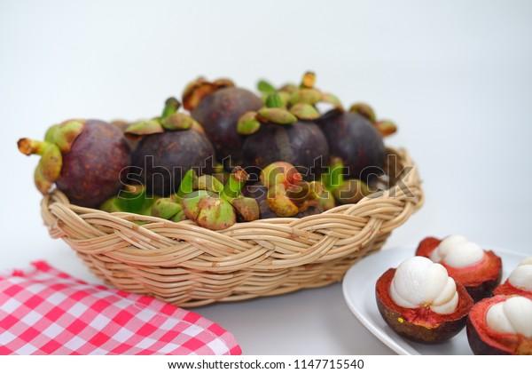 Fresh mangosteen in basket on white background