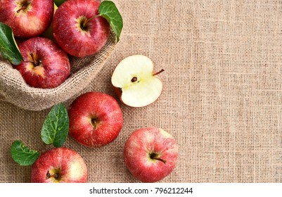 Fresh many Gala apple with green leaf with water drop in sack bag and sack background.
