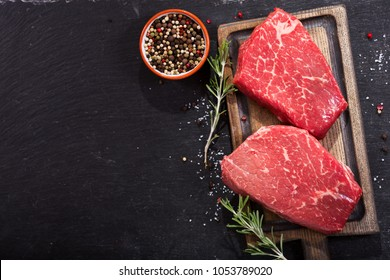 fresh meat with ingredients for cooking on dark background, top view