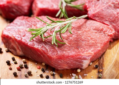 fresh meat with ingredients for cooking on wooden table