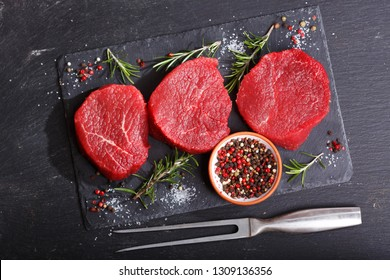 fresh meat with ingredients for cooking on dark board, top view