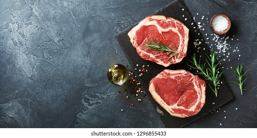 Fresh meat on slate black board top view. Raw beef steak and spices for cooking.
