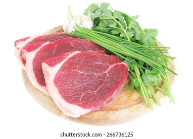 fresh meat : raw uncooked fat lamb pork fillet with green stuff and garlic on wooden plate isolated over white background