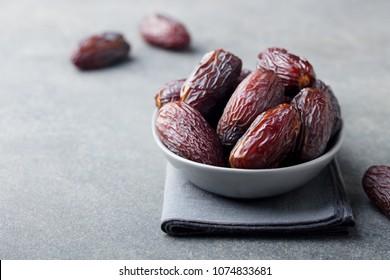 Fresh medjool dates in bowl. Grey background. Copy space.