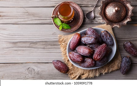 Fresh Medjool Dates in a bowl with tea. Ramadan kareem. Grey wooden background. Top view. Copy space.