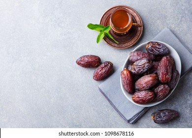 Fresh Medjool Dates in a bowl with tea. Ramadan kareem. Grey stone background. Top view. Copy space.