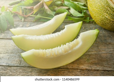 Fresh melon cut into pieces on a wooden table, selective focus and tinted image